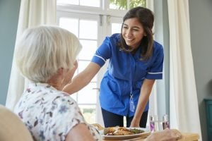 care-nurse-serving-dinner-to-a-senior-woman-at-home-300x200