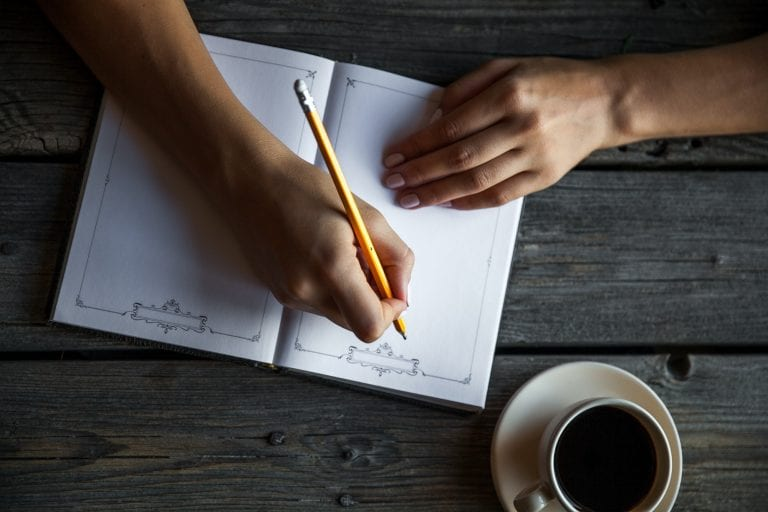 Female hand with a cup of coffee, taking notes. It works records. Business
